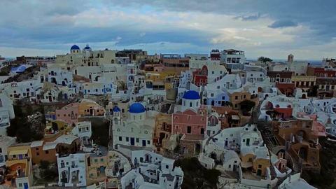 Flying over the white houses of Santorini, Greece