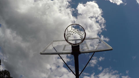 Basketball hoop against cloudy sky, time lapse 4K Footage