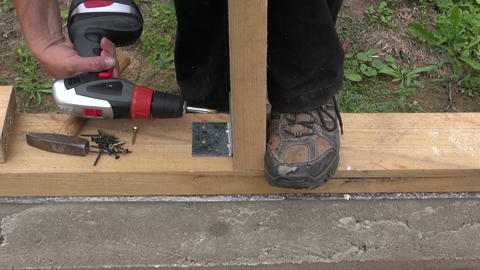Builder attaching wooden plank to foundation Footage