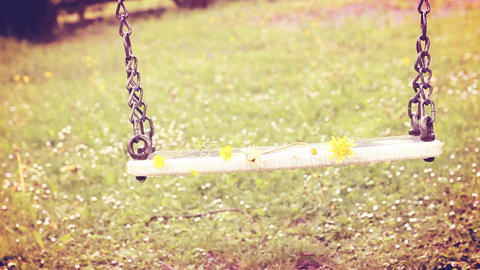 Empty swing moving with flowers in the spring season with warm creamy colors Filmmaterial