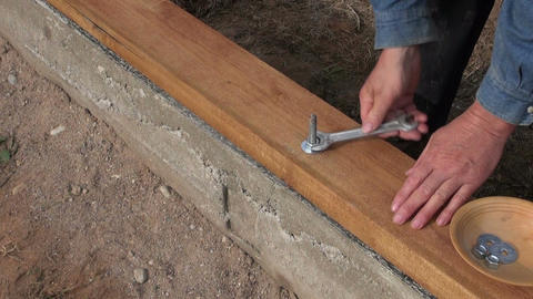 Builder fixing wooden plank with anchor on foundation Footage