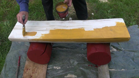Man painting wooden bench Live Action