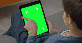 Boy using Tablet pc touchpad computer with Green Screen sitting on sofa Archivo
