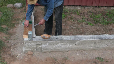 Builder securing wooden planks on cement foundation Live Action