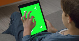 Boy using Tablet pc touchpad computer with Green Screen sitting on sofa ビデオ