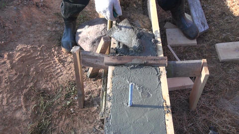 Worker cementing foundation Footage