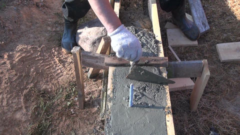 Worker cementing foundation with trowel Footage