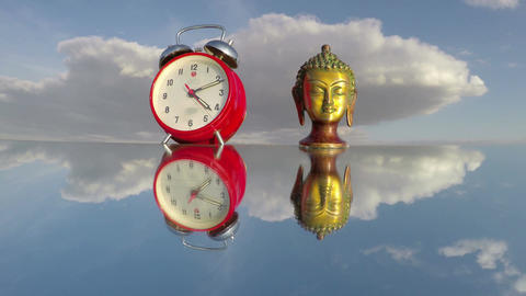 Buddha head sculpture and red clock on mirror, time lapse 4K Footage