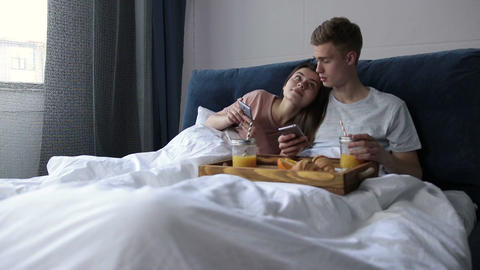 Cute couple surfing net with smartphones in bed GIF