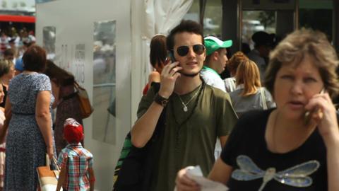 Joyful Man Walks Through Crowd and Talks on Phone Footage