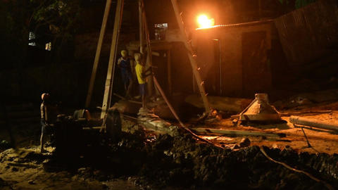 Indian workers supervising piling work done at site, at late night Live Action