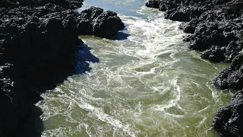 The river flows through a rocky shore Footage
