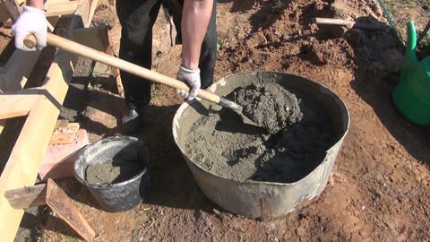Man worker shoveling concrete cement into bucket Footage