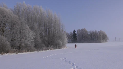 Photographer walking through snow covered field taking photos Footage