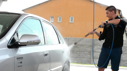 Man washing car with water (spray hose) Footage