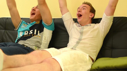 Two Friends Sitting On A Couch And Talking & Watching TV - Celebration Goal stock footage