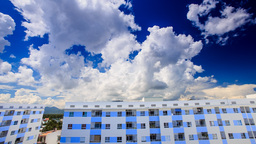 cumulus clouds motion in blue sky over high buildings Footage