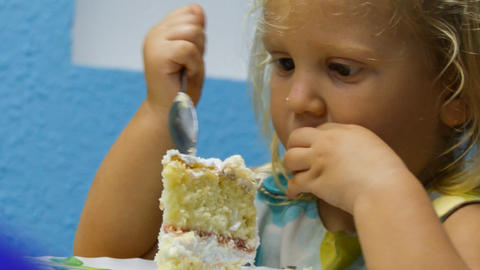 closeup little girl eats piece of birthday cake with tea spoon Footage