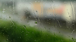rain - water drops on the window(glass). City in background (blurred shot) Footage