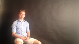 man sits in the studio and smiles - black background Footage