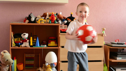 child(small boy) plays with ball and jump in the room - toys(ball) Footage