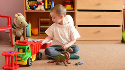 child(small boy) plays with toys in the room - toys(dragon with cars) Footage