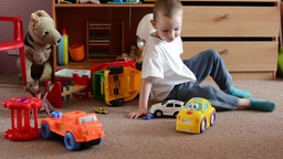 child(small boy) plays with toys in the room - toys(cars) Footage