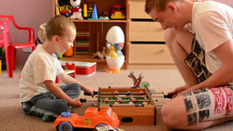 Young man plays with child (small boy) in the room - they play table football Footage