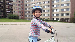 A child rides a bike on the playground and smiles - in the background houses Footage