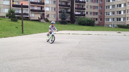 A child rides a bike on the playground - in the background houses Footage
