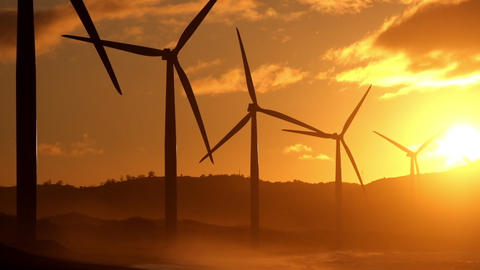 Wind turbine power generators silhouettes at stormy ocean coastline at sunset Footage