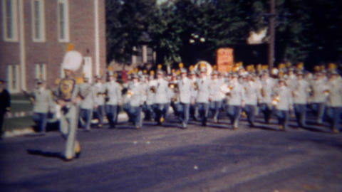 1952: Gray marching band plays music down campus street Footage