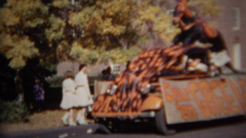 1952: Students walking by high school campus while parade float goes by Footage
