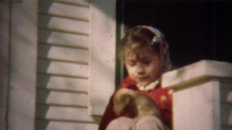 1948: Cute girl bundled up for fall plays with golden retriever puppy Live Action