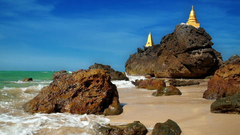 Slow motion waves at tropical sandy beach near amazing Buddhist Pagodas on rock  Footage