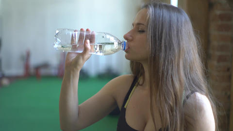 Young Woman Has Rest Drinking Water In Gym Footage