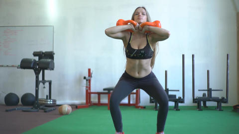 Young Woman In Crossfit Gym Doing Squats With Kettlebells Footage