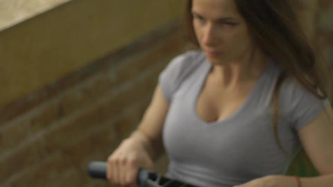 Woman Working Out On Rowing Machine At The Gym