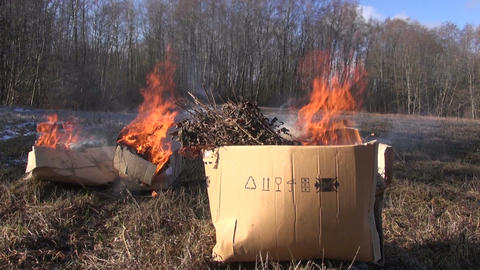 Brown cardboard boxes with organic rubbish burning in field Footage