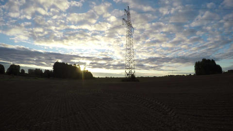 Sunrise on cloudy morning over field with electrical pylon, time lapse 4K Footage