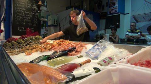 Man collecting large shrimps in the plastic bag in fish market Footage