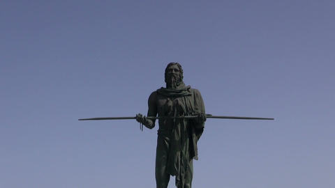 TENE Sculpture of guanche with two birds on a stick and a man walking by on ocea Footage