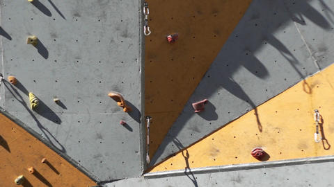 Slow Motion Tilting Up Along An Outdoor Climbing Wall Footage