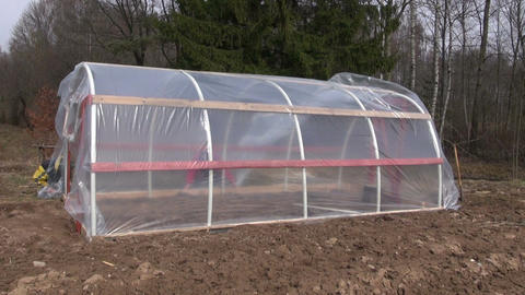 Two workers building polyethylene greenhouse Footage