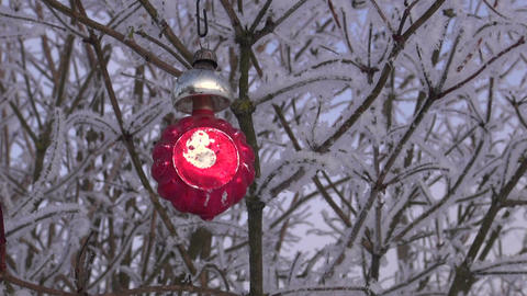 Vintage Christmas ornament hanging on hoarfrost covered shrub branch outdoors Live Action