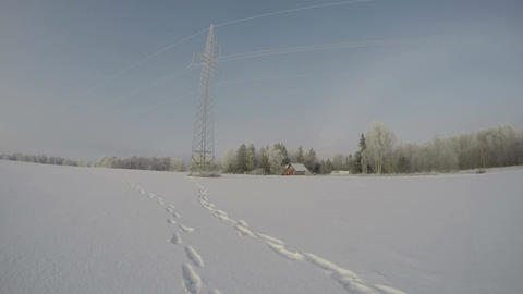 Landscape with electrical pylon and red homestead during snowdrift, time lapse 4 Footage