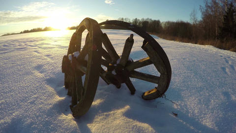 Two antique wooden wheels in the snow during sunset, time lapse 4K Footage