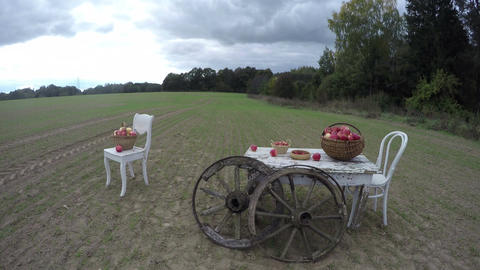 Two white chairs and a table with apples in wicker baskets with two antique wood Footage