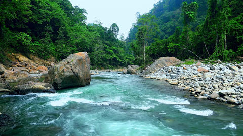 Stony bed of beautiful aquamarine mountain river running in dense jungle Footage