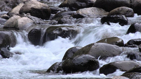 River streaming among smooth boulders. Mountainous watercourse in North Sumatra Footage